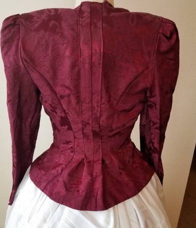 back of jacket shaped--pleat at the center back, curved seams taken in
