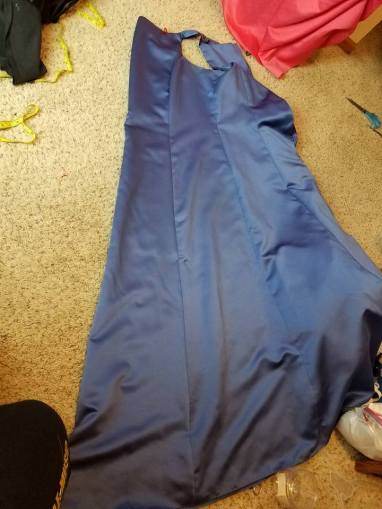 folding the blue dress before slitting up the center front