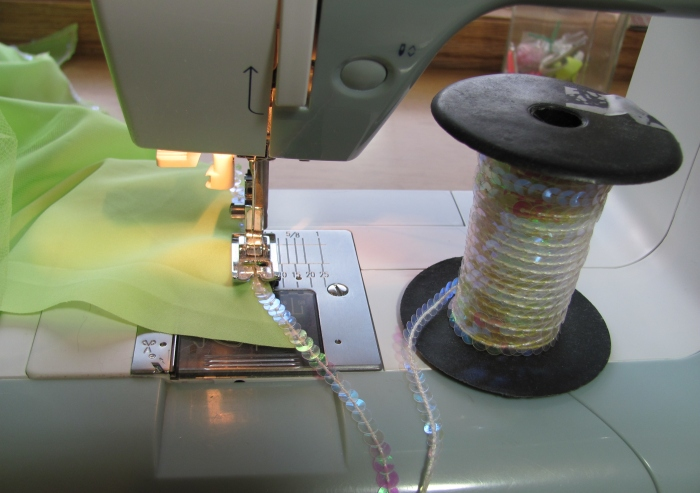 adding string sequins to the edge of the skirt