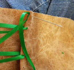 using a large needle to thread the ribbon, holes punched beforehand