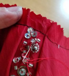 hand securing the beads where the threads were cut for the seams
