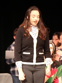 Shy--in a conservative sweater and high necked polka dot blouse